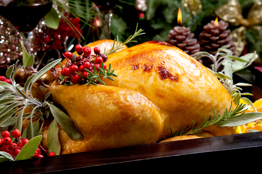 Roasted turkey garnished with sage rosemary and red berries in a tray prepared for Christmas dinner. Holiday table candles and Christmas tree with ornaments.